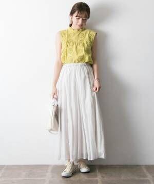 イエローのアイレット刺繍のハイネックブラウスに白のスカートを合わせた女性