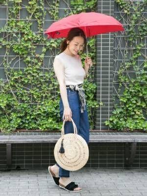 ノースリーブにデニムパンツを履き傘を持った女性