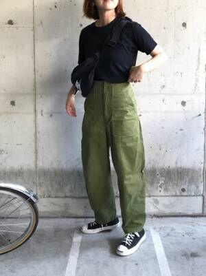 黒のトップスにカーキのベイカーパンツを履いた女性