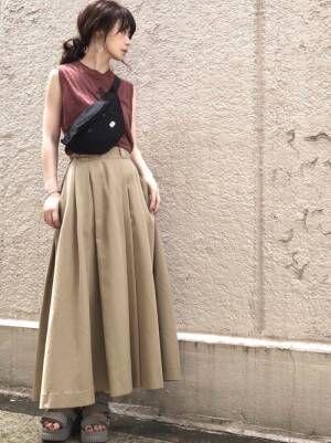 ブラウンのトップスにベージュのタックフレアスカートを履いた女性