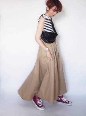 ボーダートップスにベージュのフレアスカートを履いた女性