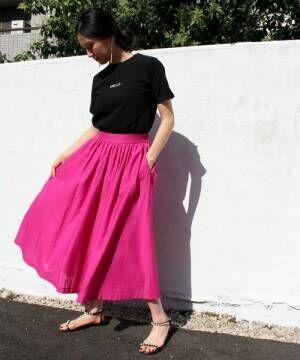 黒のチビロゴTシャツにピンクのフレアスカートを合わせた女性