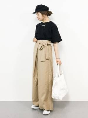 黒のチビロゴTシャツにベージュのハイウエストのベルト付きパンツを合わせた女性