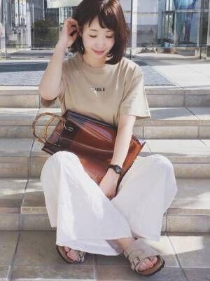ベージュのチビロゴTシャツに白の刺繍パンツを合わせた女性