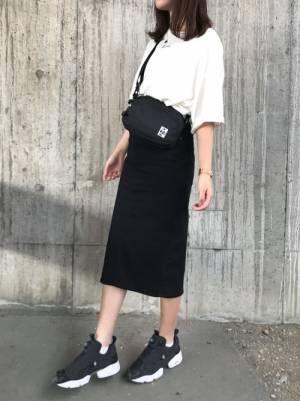 白のチビロゴTシャツに黒のタイトスカートを合わせた女性