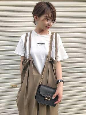 白のチビロゴTシャツにカーキのサロペットスカートを合わせた女性
