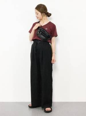 ワインレッドのチビロゴTシャツに黒のワイドパンツを合わせた女性