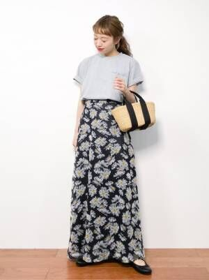 グレーのチビロゴTシャツに黒ベースの花柄スカートを合わせた女性