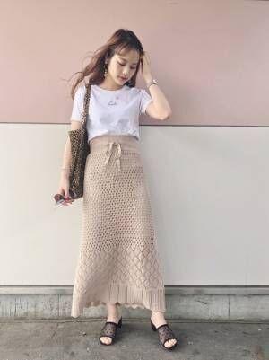 白のチビロゴTシャツにベージュのニットスカートを合わせた女性