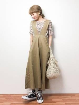 小花柄インナーにカーキトラペーズワンピでベージュ鍵編み鞄を持ち黒スニーカを合わせた女性