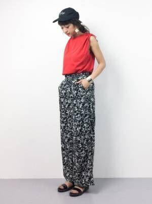 黒キャップを被って赤のトップスに花柄ボトムスを履いた女性