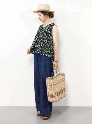花柄ノースリーブトップスにパンツと夏らしい小物を合わせた女性