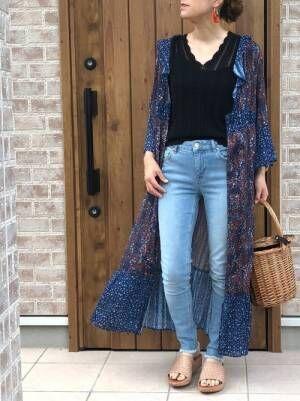 花柄ガウンにタンクトップとデニムパンツを履いた女性