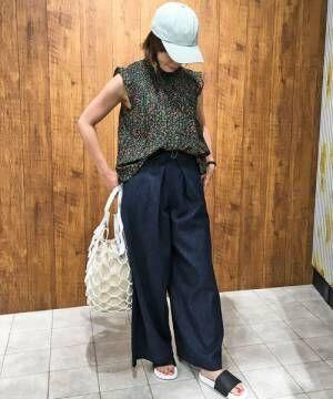 花柄ノースリーブにワイドパンツにキャップとサンダルを履いた女性