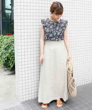 花柄フリルノースリブラウスに白スカートを履いた女性