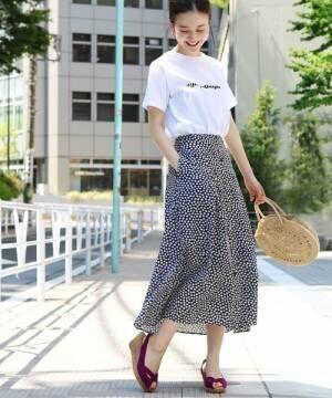 白ロゴTシャツに花柄スカートを履いた女性