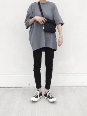グレーTシャツに黒スキニーを履いた女性