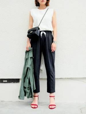 白のタンクトップに黒のテーパードパンツを履いた女性