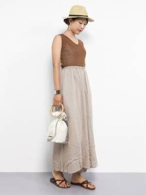 ブラウンのタンクトップにベージュのワイドパンツを履いた女性