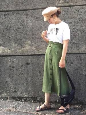 白のロゴTシャツをカーキのベルト付きフロントボタンスカートにINした女性