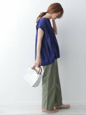 ブルーのブラウスをカーキのパンツにOUTして着た女性