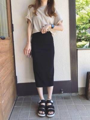 ベージュのTシャツを黒のタイトスカートにゆるっとINした女性