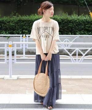 ベージュのTシャツをドット柄のスカートにOUTして着た女性