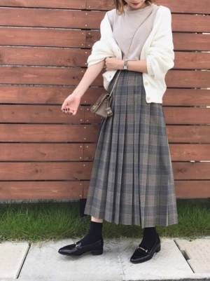 ベージュのTシャツに白のカーディガンを羽織って、チェック柄のプリーツスカートを合わせた女性