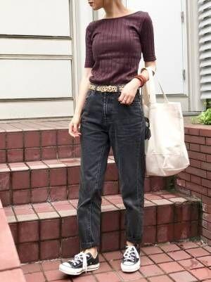 ブラウンのリブTシャツにブラックデニムを合わせて、レオパード柄のベルトをした女性