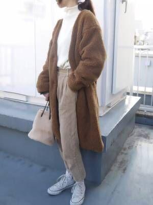 白ニットとベージュパンツにブラウンコートの女性