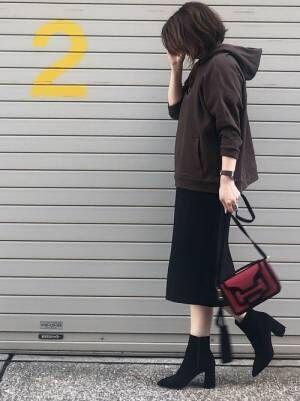 ブラウンのパーカーに黒のタイトスカートを合わせた女性