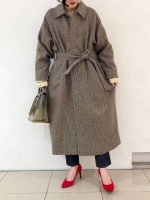 デニムパンツとコートに赤いパンプスの女性