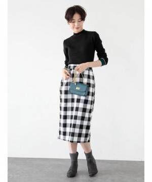 黒にグリーンのラインが入ったハイネックタイプのラインニットにギンガムチェックのタイトスカートを合わせた女性