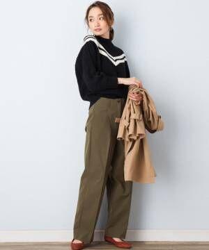 白のラインが入った黒のモックネックタイプのラインニットにカーキのパンツを合わせた女性