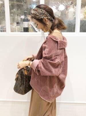 ZARAのピンクのコーデュロイジャケットを羽織って、レオパード柄のヘアバンドをした女性