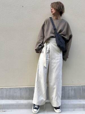 ZARAのベージュのスウェットに白のワイドパンツを合わせた女性
