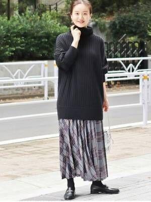 黒のタートルネックニットにブルーベースのチェック柄スカートを合わせた女性