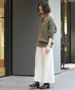 グレーのVネックニットにキナリのプリーツスカートを合わせた女性