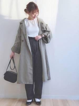 白のトップス、黒のデニムパンツにカーキのトレンチコートを着た女性