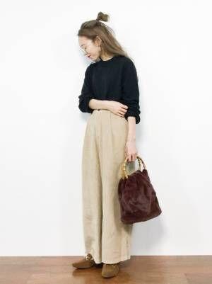 黒ニットにベージュのパンツを合わせて、キャメルのローファーを履いた女性