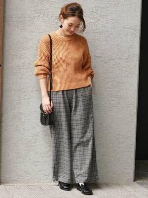 オレンジのニットにグレーのチェックパンツを合わせて、黒のローファーを履いた女性