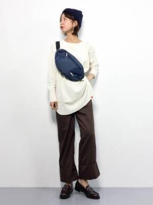ベージュのサーマルTシャツにダークブラウンのパンツを合わせて、黒のローファーを履いた女性