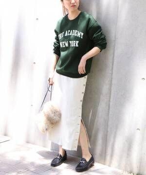 ロゴスウェットに白スカートとローファーを履いた女性