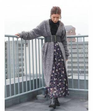 黒のタートルニットにネイビーの花柄スカートを合わせて、グレーのブークレニットのロング丈カーディガンを羽織ってベルトをした女性