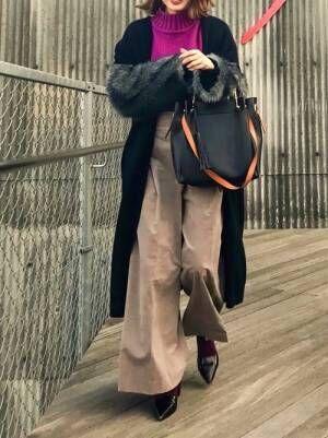 パープルのニットにグレーのワイドパンツを合わせて、黒のファースリーブのロング丈カーディガンを羽織った女性
