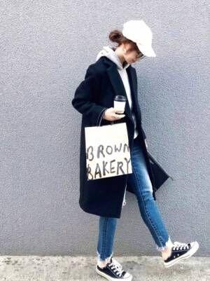 パーカーにネイビーのチェスターコート、デニムパンツを穿きキャップを被ったコーデ