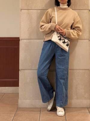 白のタートルネックの上にスウェットを合わせ、デニムパンツを穿いたコーデ