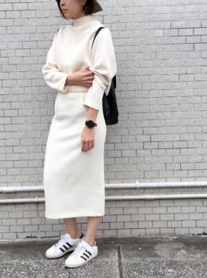 白のニットセットアップを着た女性