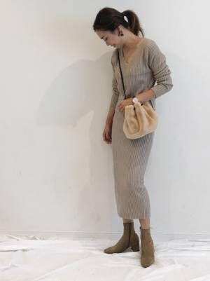 ピンクベージュのニットとタイトスカートのセットアップを着た女性
