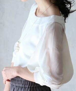 腕だけシースルーの白トップスを着た女性